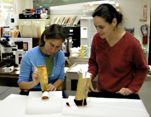 Lauren Horelick (left) treats a pair of Aleut/Alutiiq boots with help from her supervisor, conservator Ellen Carrllee (right)